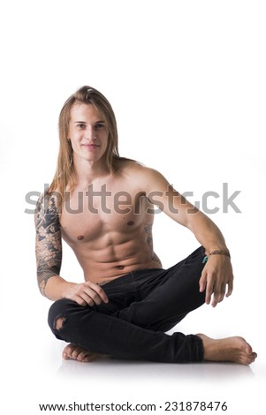 Beautiful young long haired man shirtless, sitting on the floor smiling, posing isolated - stock photo