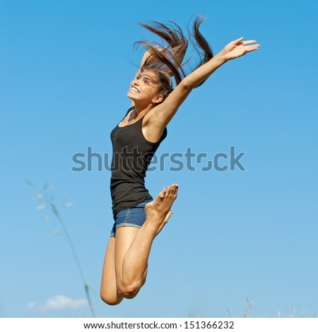 beautiful young long-haired woman jumping up background summer blue sky clouds - stock photo