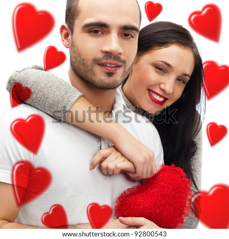 Beautiful young love couple embracing against a white background and many red hearts flying around them