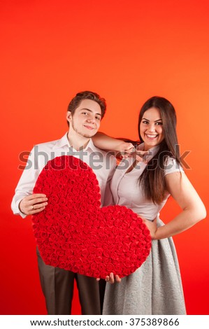 Beautiful young love couple embracing against red background