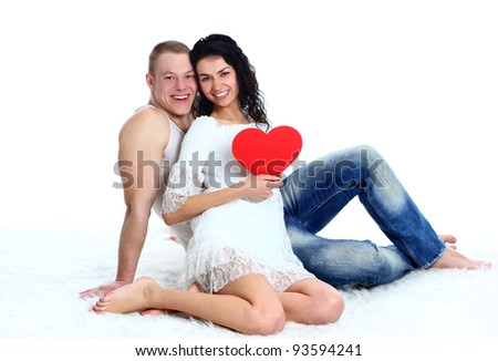 Beautiful young love couple sitting on the floor with a big red heart on white background - stock photo