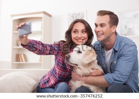 Beautiful young loving couple is making selfie with their dog. They are sitting on sofa and smiling. The woman is holding a mobile phone - stock photo