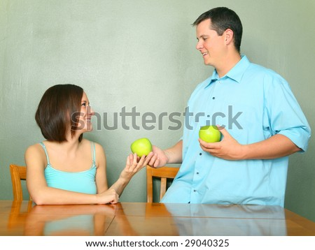beautiful young male caucasian offering green apple to his girlfriend or wife on kitchen table