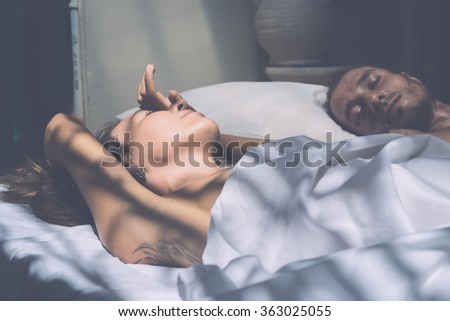 beautiful young man and woman in the morning in bed . Gentle morning together.  (author's style treatment of light and color)