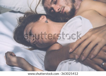 beautiful young man and woman in the morning in bed . Gentle morning together.  (author's style treatment of light and color) - stock photo