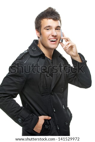 Beautiful young man in black clothes laughs and talks by mobile phone. - stock photo