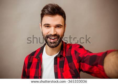 Beautiful young man with a beard in checkered shirt makes self, smiling, on a gray background - stock photo