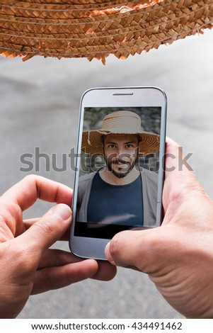 Beautiful young man with a straw hat, taking a selfie - stock photo