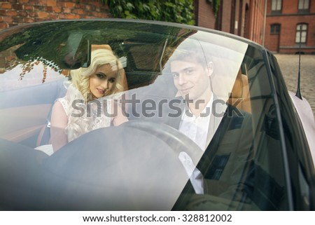 Beautiful young married couple sitting in cabrio car - stock photo