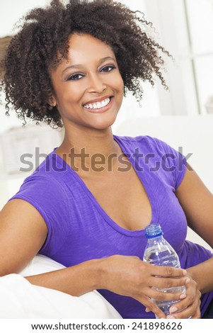 Beautiful young mixed race black African American woman smiling, relaxing and drinking a bottle of water at home on a sofa - stock photo
