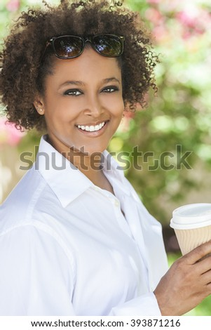 Beautiful young mixed race black African American woman smiling wearing sunglasses drinking a takeaway cup of coffee outside - stock photo