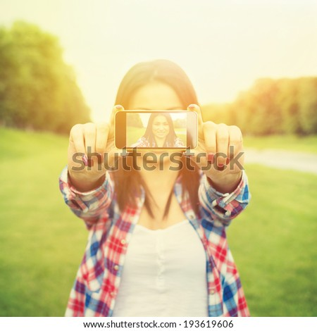 Beautiful young mixed race woman taking a selfie portrait photo with smart phone. Instant looking filter. Square image format.  - stock photo