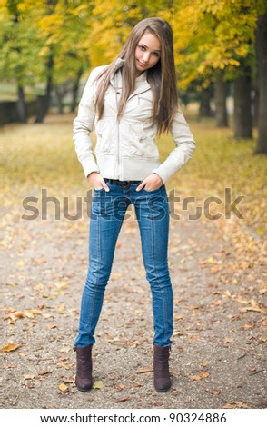 Beautiful young model dressed for chilly weather posing outdoors in the park. - stock photo