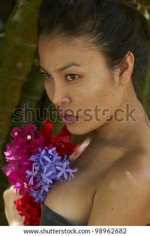 Beautiful young model from Thailand holding colorful fresh flowers standing in front of bamboo trees. - stock photo