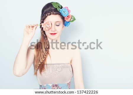 beautiful young model holding a pink rose in front of her right eye and closing her other eye on blue background - stock photo