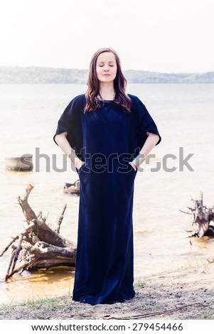Beautiful young model in long navy blue dress posing at summer beach near water - stock photo