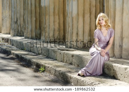 beautiful young model sitting near old columns - stock photo
