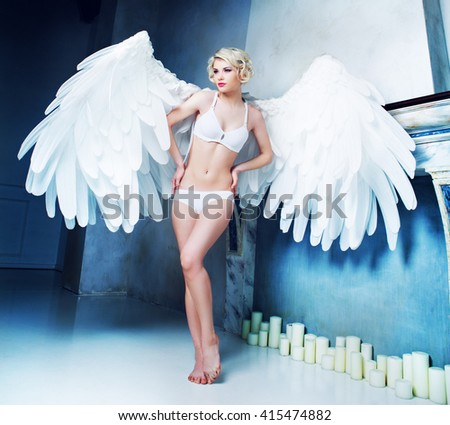 beautiful young model wearing white underwear with angel wings in the studio - stock photo