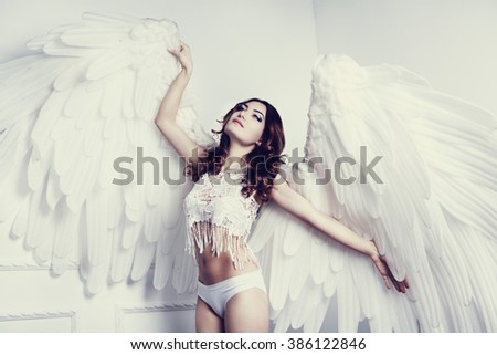 beautiful young model with angel wings in the studio - stock photo