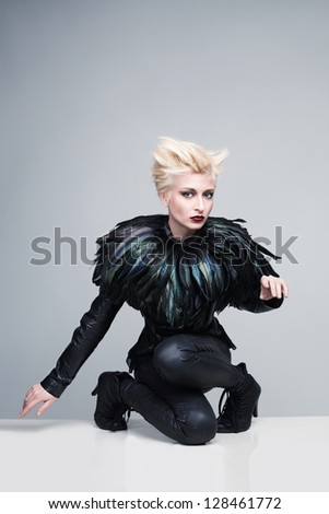 beautiful young model with futuristic leather clothes and feathers posing and looking at camera - stock photo