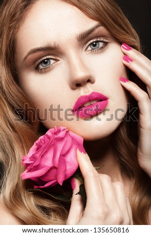 Beautiful young model with pink rose, bright makeup and manicure - stock photo