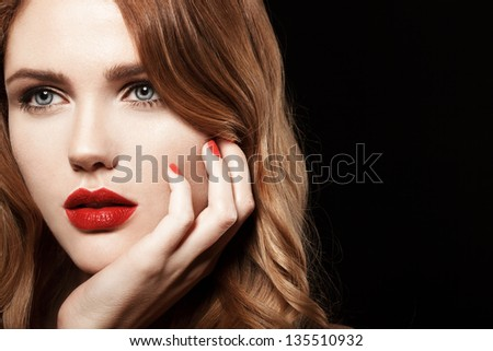 Beautiful young model with red lips and red manicure on black background - stock photo