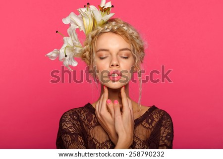 Beautiful young model with white flowers, bright makeup and manicure. Pink background. Fashion studio shot. red big lips. - stock photo