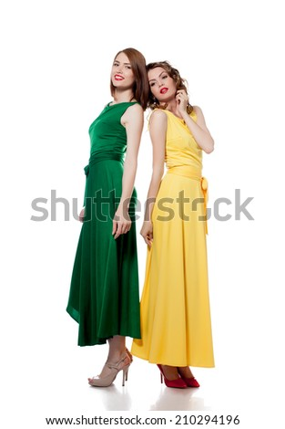Beautiful young models posing in colorful dresses - stock photo