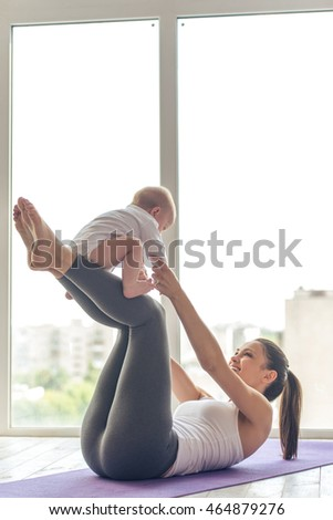 Beautiful young mom in sports wear is smiling while working out with her charming little baby on yoga mat against window