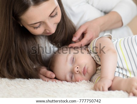 Beautiful young mom looking at her cute little baby sleeping in bed at home
