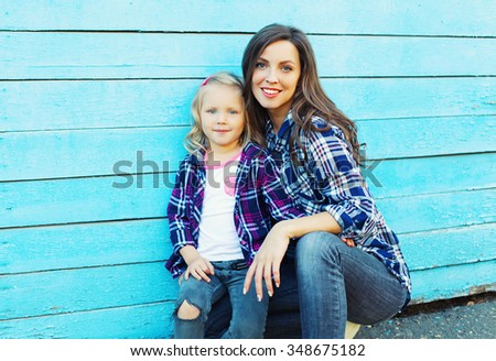 Beautiful young mother and child daughter in city over blue background - stock photo