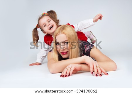Beautiful young mother and daughter playful - stock photo