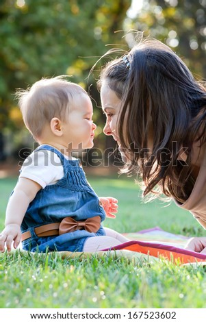 Beautiful young mother and her cute baby in the park.