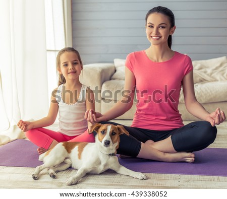Beautiful young mother and her cute little daughter are looking at camera and smiling while sitting in lotus pose with their dog on yoga mat at home - stock photo