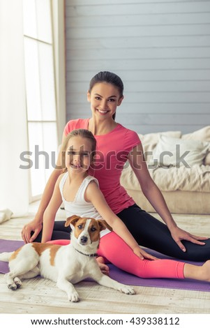 Beautiful young mother and her cute little daughter are stretching and smiling while sitting in with their dog on yoga mat at home - stock photo