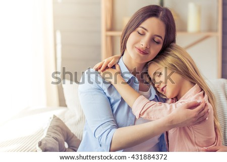 Beautiful young mother and her daughter are hugging and smiling while sitting with closed eyes on the sofa at home - stock photo