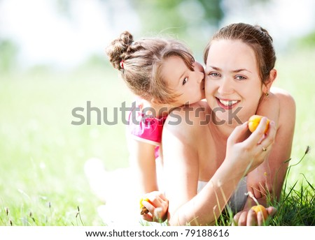 beautiful young mother and her daughter eating pears in the park on a sunny summer day (focus on the woman)