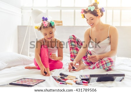 Beautiful young mother and her daughter in pajamas and with hair curlers are doing pedicure and smiling, sitting on bed at home - stock photo