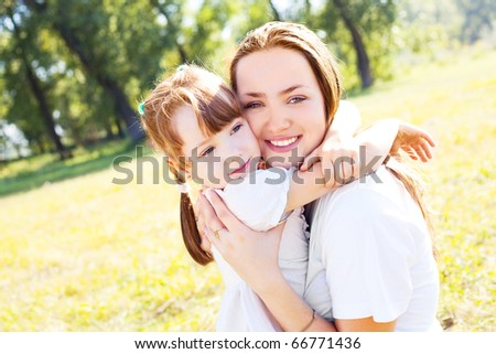 beautiful young mother and her daughter in the park on a sunny autumn day - stock photo