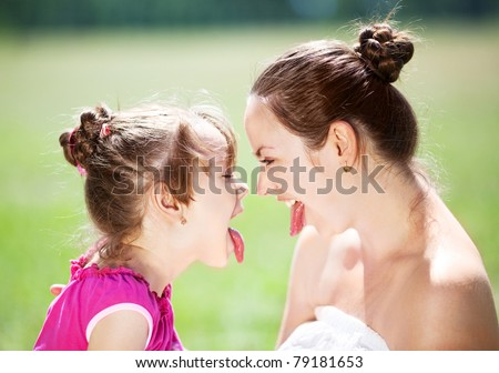 beautiful young mother and her daughter in the park on a sunny summer day  having fun and showing tongue (focus on the woman) - stock photo