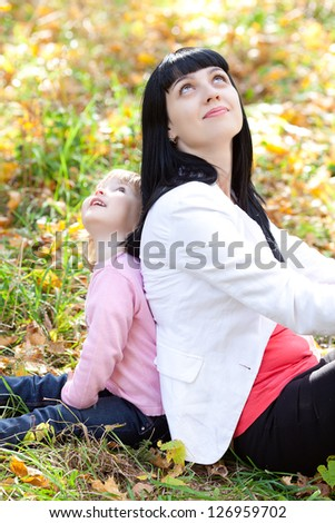 beautiful young mother and her daughter looking up in the autumn forest