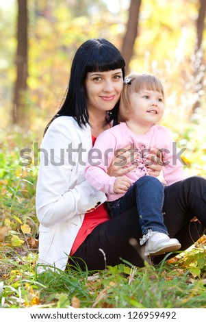 beautiful young mother and her daughter on the autumn forest