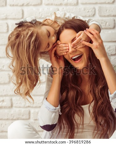 Beautiful young mother and her little daughter are smiling, sitting against white brick wall. Girl is closing her mother eyes - stock photo