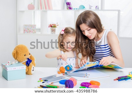 beautiful young mother and her little daughter drawing with crayons on the album. mother and daughter having fun at home. - stock photo