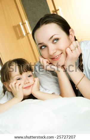 beautiful young mother and her little daughter on the bed dreaming of something - stock photo