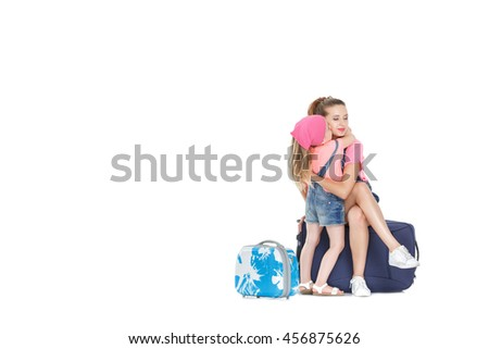 beautiful young mother and lovely daughter is going on a trip. woman and child with a suitcase on castors on white background - stock photo