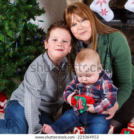 Beautiful young mother and two adorable sibling boys with Christmas tree and decoration. Square format.