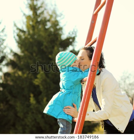 Beautiful young mother doing fitness with his little daughter at the playground - stock photo