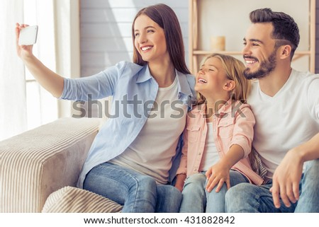 Beautiful young mother, father and their daughter are making selfie using a phone and smiling while sitting on the sofa at home - stock photo