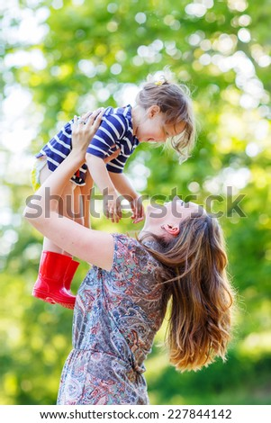 Beautiful young mother holding her happy little kid girl in arms in red rain boots in summer park on sunny warm day. Happy family: mom and daughter concept. - stock photo